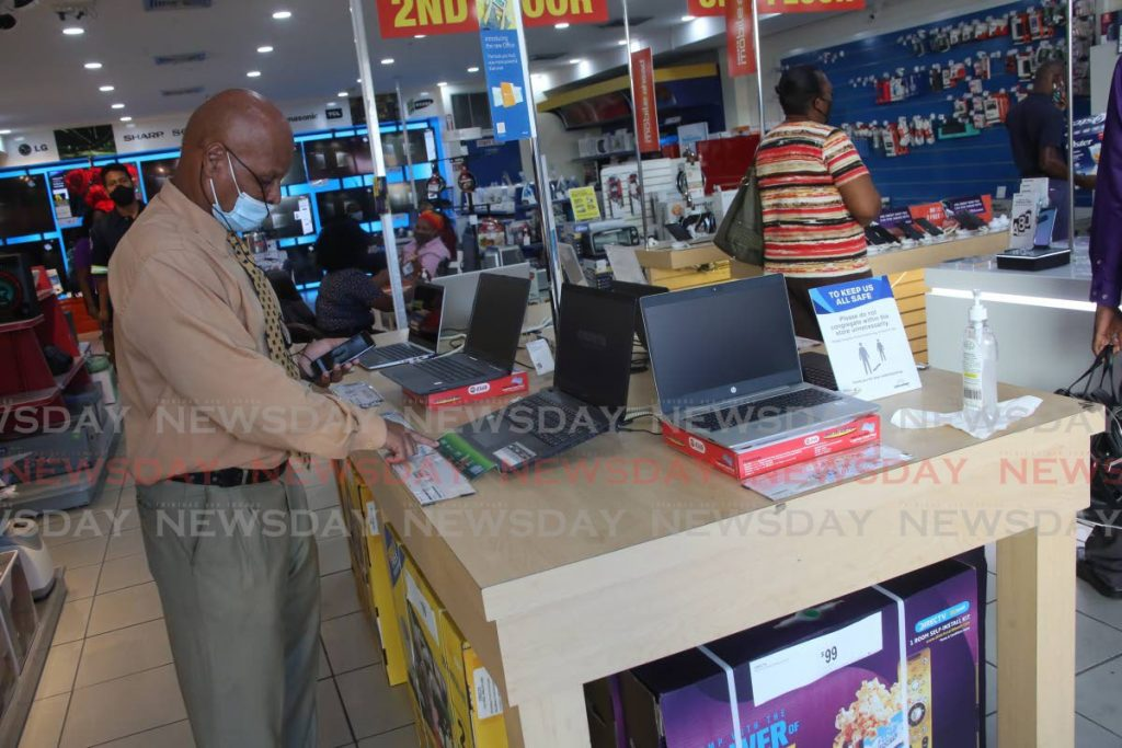 A man looks at laptops on display at a Courts outlet on Frederick Street. - Sureash Cholai