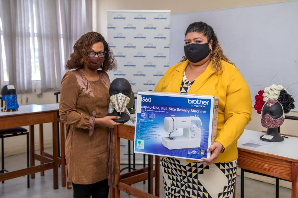 Fashion design student Hannah Timothy receives a Brother sewing machine from a representative for her mask design during a presentation at UTT, Wrightson Road, Port of Spain on August 26. Timothy placed second in a competition organised by Port of Spain Fashion Week. Photo courtesy Unicomer (Trinidad) Ltd. -