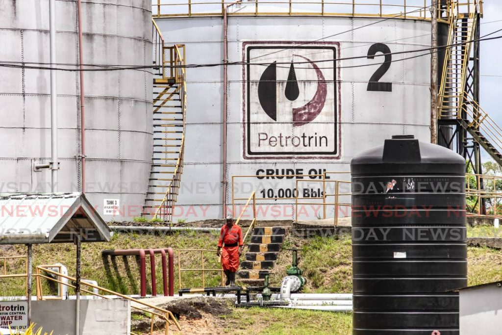 In this September 9, 2018 file photo an employee walks past a storage tank at the Petrotrin Point Fortin Central Tank Farm  and Oil Transfer Facility. Petrotrin was closed in 2019 and its assets now fall under Trinidad Petroleum Holdings. The Energy Ministry announced on Wednesday a significant increase in oil reserves based on a 2018 audit. PHOTO BY JEFF K MAYERS  -