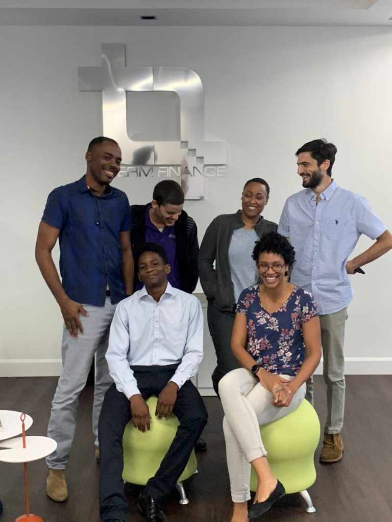 In this January file photo, 17-year-old Pleasantville Secondary School student Yohance Rivas (seated, left) is surrounded by staff of Term Finance as he begins a scholarship at the company. The budding entrepreneur earned an open one-year internship from CEO Oliver Sabga after the two interacted at a TecYOUth event the previous November. -