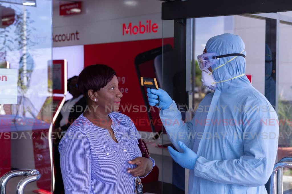 In this March file photo, a customer at Digicel's Shirvan Plaza, Tobago branch has her temperature checked as a preventive measure against the spread of covid19. Four days the August 10 general election, the government announced that 'pandemic leave' was to be granted to all government employees. - FILE PHOTO