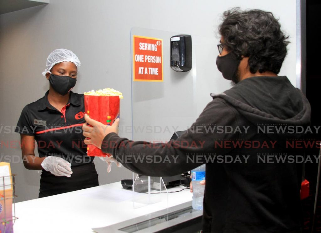 Customer Justin Baldeosingh receives his popcorn from CSR Melissa Garcia as Caribbean Cinemas 8 reopened for business  after the covid19 lockdown on June 25. Amcham applauds Government's management of the pandemic as it proposes ways for the country to go forward. - Ayanna Kinsale