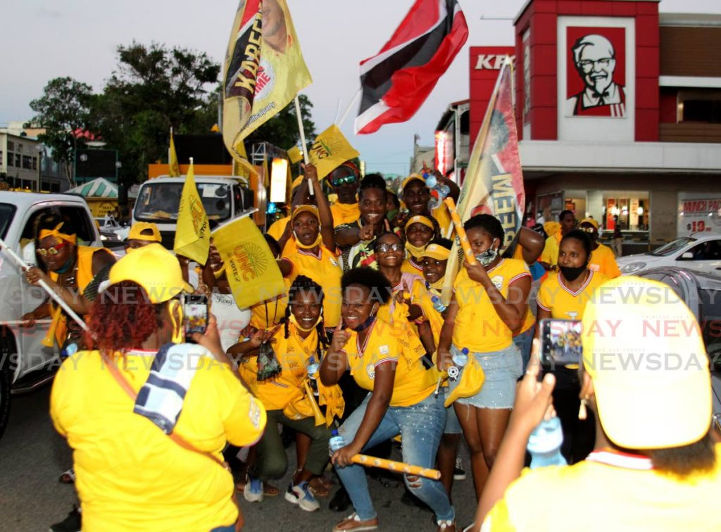 UNC Candidate for Laventille East Morvant Kareem Baird, centre stops to take a photo with his supporters at KFC, Independence Square, Port of Spain during a motorcade on Friday. - ROGER JACOB