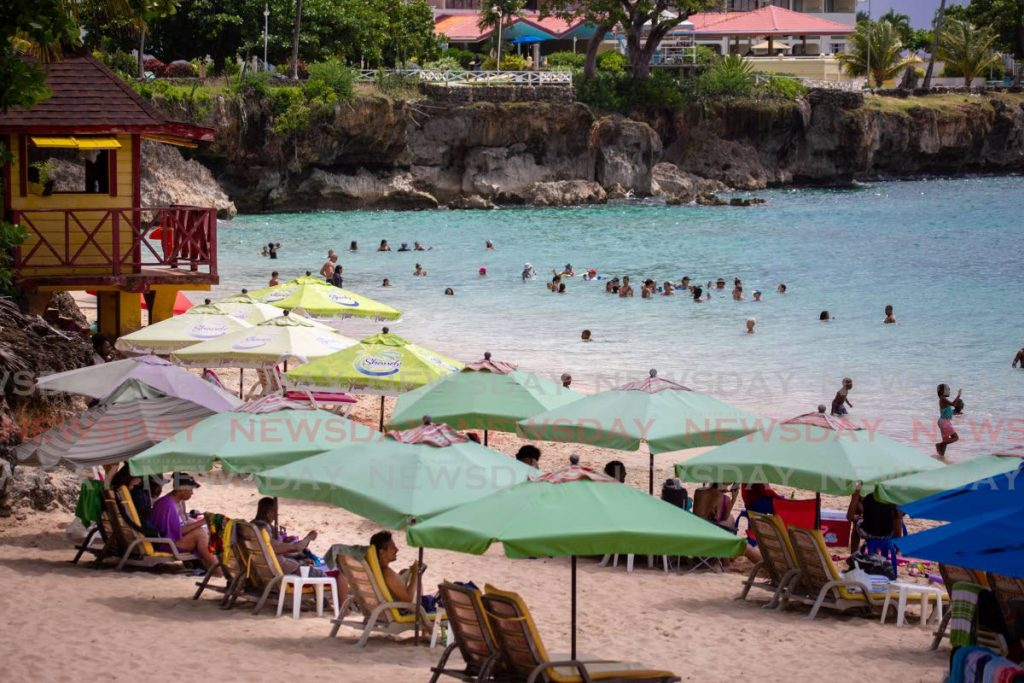 LAST DIP: People flocked to Store Bay on August 16 ahead of the Government's closure of all beaches and rivers to stop the spread of covid19. PHOTO BY DAVID REID -