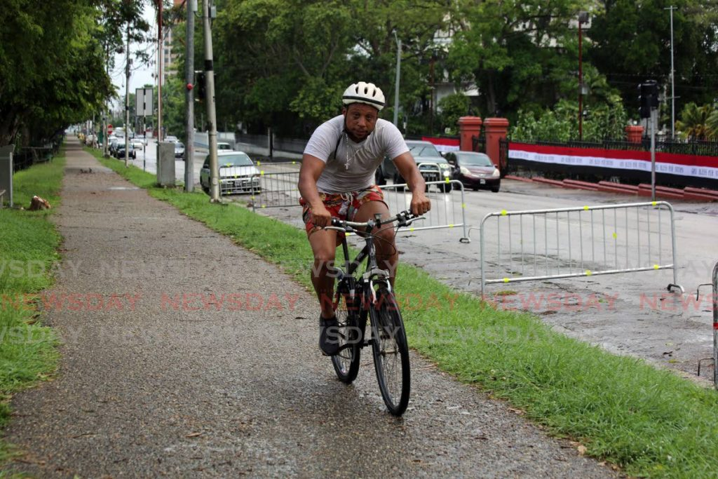 A cyclist rides, with his face mask under his chin, around Queen's Park Savannah, Port of Spain recently. Health Minister Terrence Deyalsingh on Saturday said people exercising in public can use a face shield instead of a mask.  - SUREASH CHOLAI