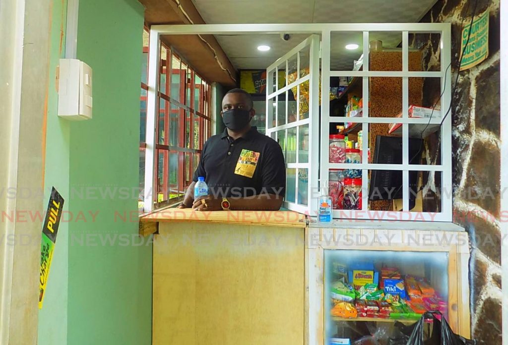 David Hartman sits behind the counter of his Marie Road, Morvant, mini mart. Hartman toyed with the idea of opening his own grocery but took it seriously after his daughter's birth seven yeas ago and the death of his mother last January. - Shane Superville