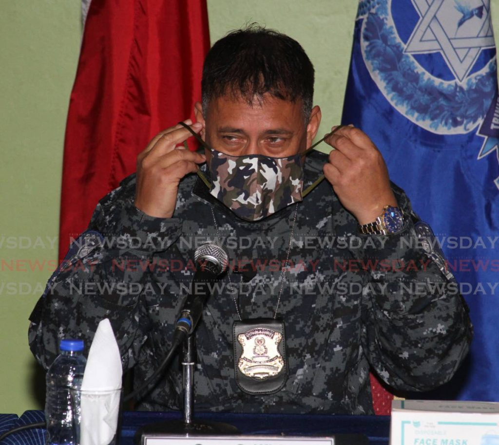 Police Commissioner Gary Griffith puts on his mask during a media briefing at the Police Administration Building in Port of Spain. - Angelo Marcelle