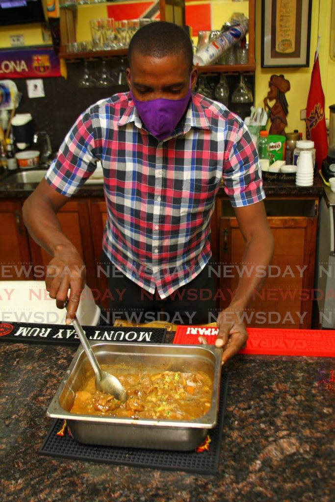 Garth Leith, an employee of Pancho's on Edward Street, Port of Spain, lays out a pan of stewed oxtail just before midday on September 4. - ROGER JACOB