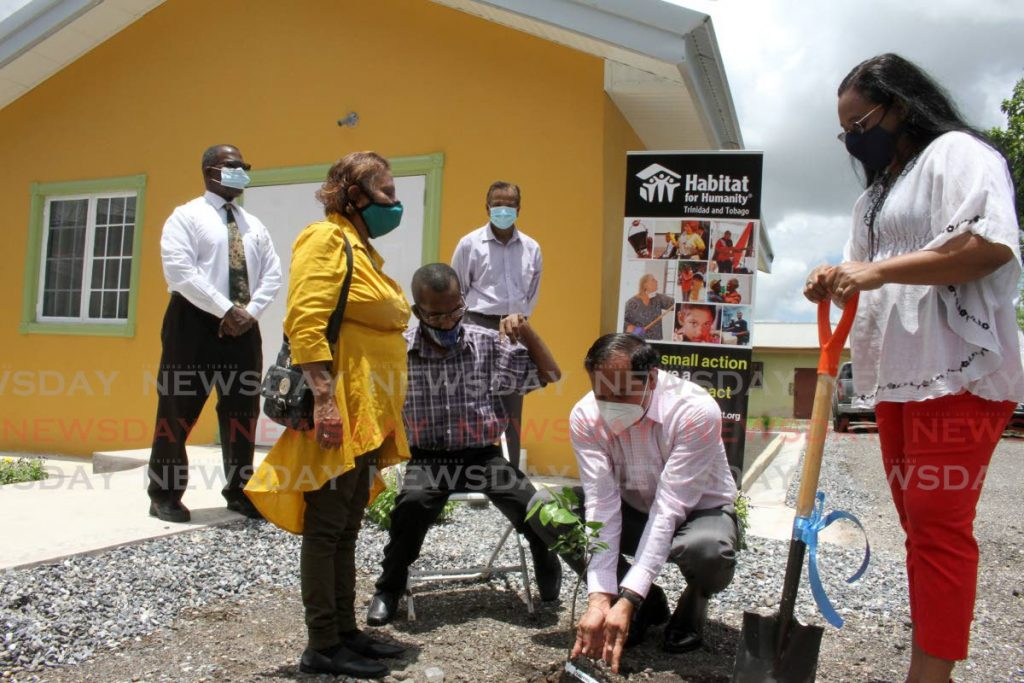 Habitat for Humanity TT chairman Sieunarine Coosal plants an orange tree in the yard of the new home in Enterprise for Angela Swamber and her son Aaron, alongside Habitat TT national director Jennifer Massiah on Friday. - PHOTOS BY ANGELO MARCELLE