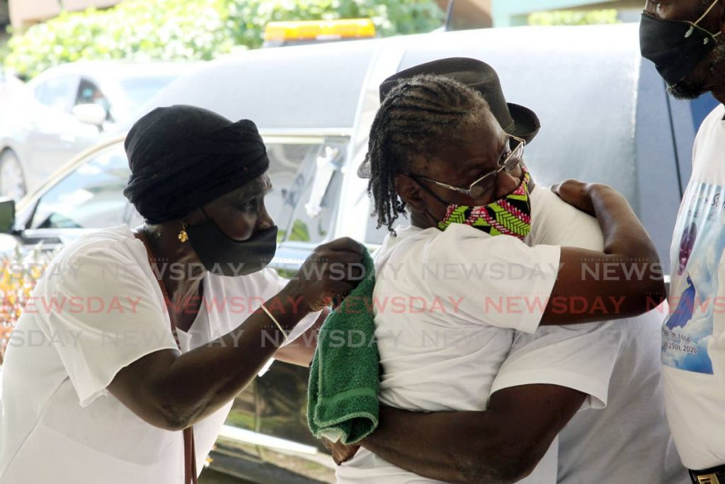 Mary Hudlin Walker, left, mother of Venrick Hudlin, who was shot and killed by an off-duty police officer on August 29, consoles relatives during his funeral at the family's home on Gomez Trace, St Mary's, Moruga on Saturday. PHOTO BY LINCOLN HOLDER -