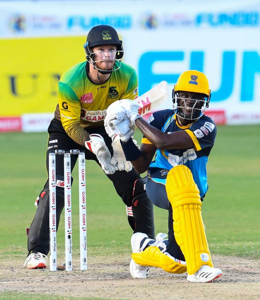 Jonathan Carter (R) of Barbados Tridents hits a four as Glenn Phillips (L) of Jamaica Tallawahs watches during the Hero Caribbean Premier League match 28 at Brian Lara Cricket Academy, Tarouba, on Saturday. - CPL T20 via Getty Images