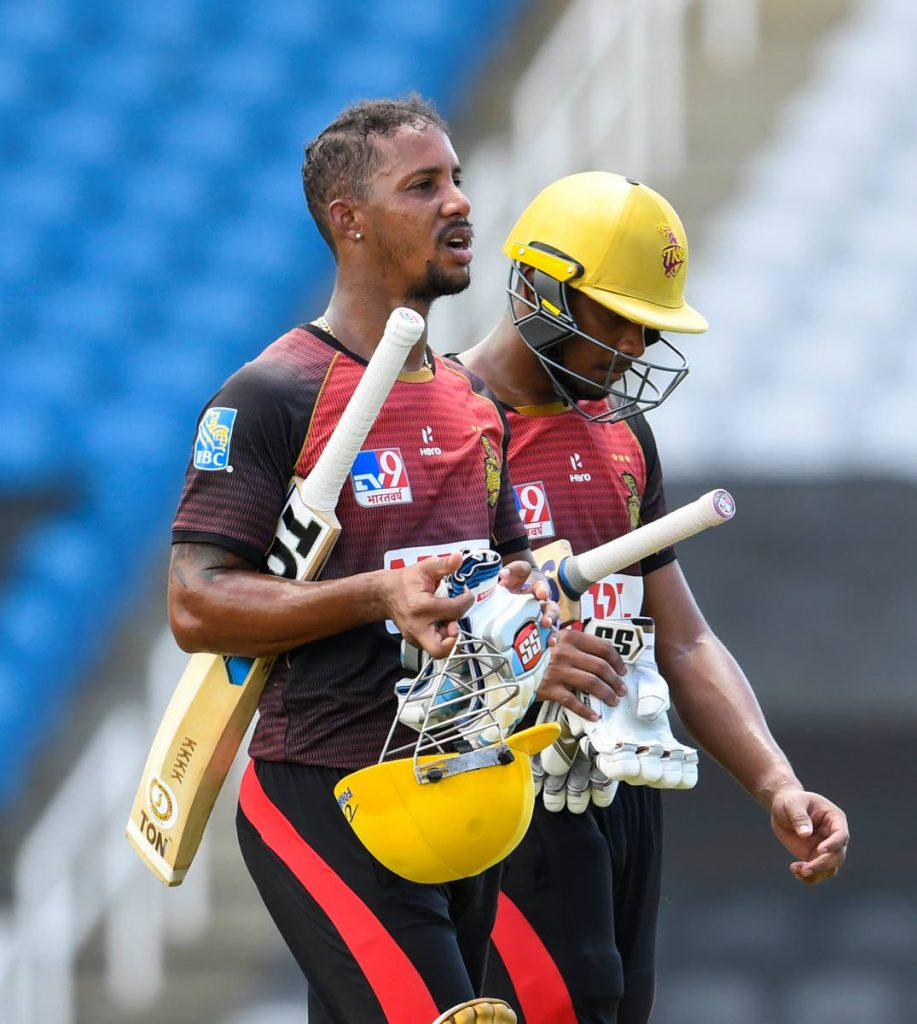 Lendl Simmons (left) and Tion Webster of Trinbago Knight Riders walk off the field after the TKR defeated the Jamaica Tallawahs in their Hero Caribbean Premier League semi-final match on Tuesday at the Brian Lara Cricket Academy, Tarouba on Tuesday. (Photo by CPL T20 via Getty Images) -