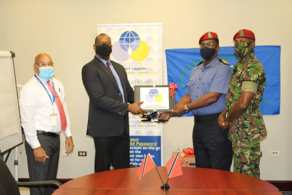 Clico Credit Union's senior business development officer Fred Vidale and CEO Niall Legerton hand over a computer to Milat's Cpt Douglas Archer and Major David R Benjamin.  Photo courtesy Clico Credit Union -