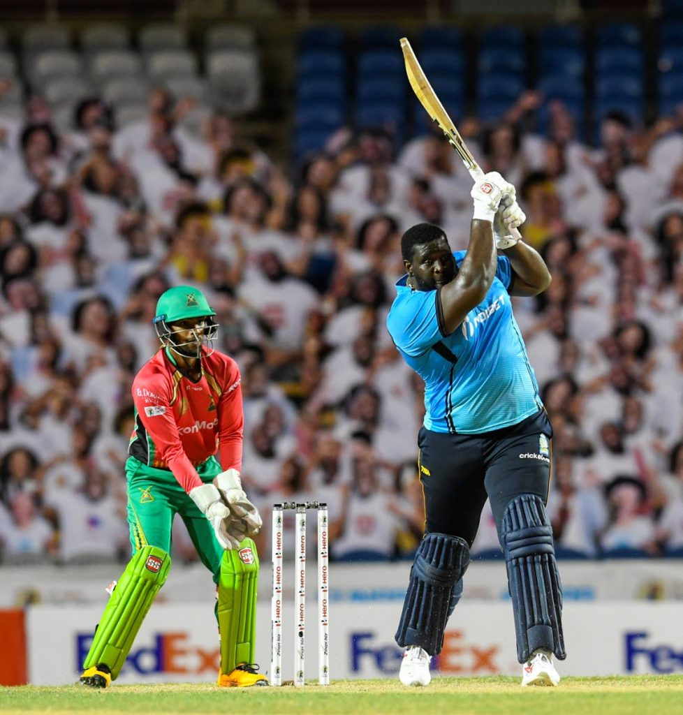 Rahkeem Cornwall (right) of St Lucia Zouks hits a six while wicket-keeper Nicholas Pooran of Guyana Amazon Warriors watch during the teams' Hero Caribbean Premier League semi-final match on Tuesday at the Brian Lara Cricket Academy in Tarouba. (Photo by CPL T20 via Getty Images) -