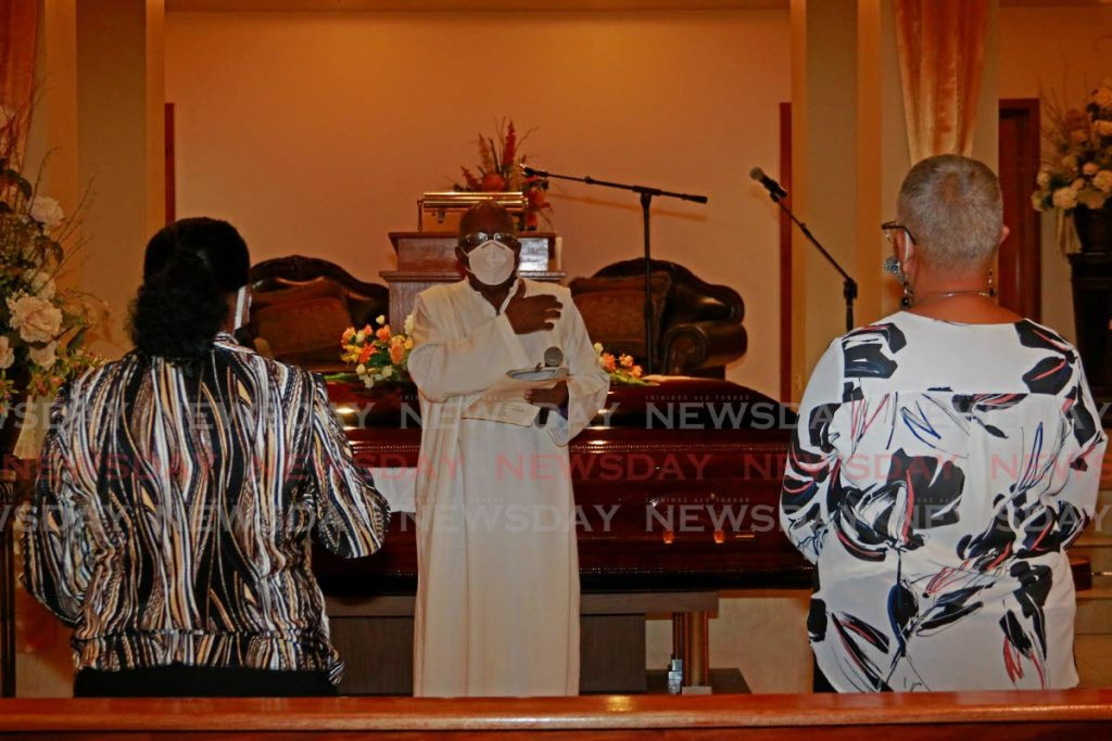 Lay minister Cecil Colthrust officiates at the funeral of Hazel  Rambaransingh on Thursday. - Marvin Hamilton