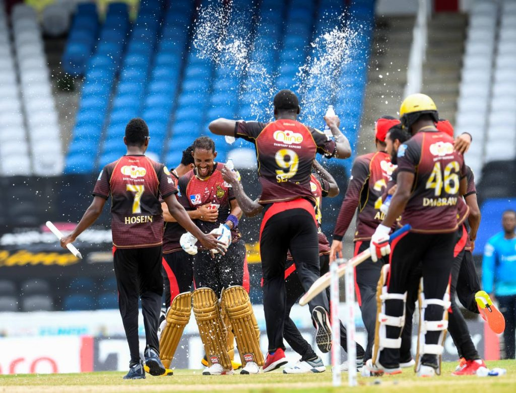 Lendl Simmons (2L) and Trinbago Knight Riders team-mates  celebrate winning the Hero Caribbean Premier League 2020, at Brian Lara Cricket Academy,Tarouba, on Thursday. - CPL T20 via Getty Images