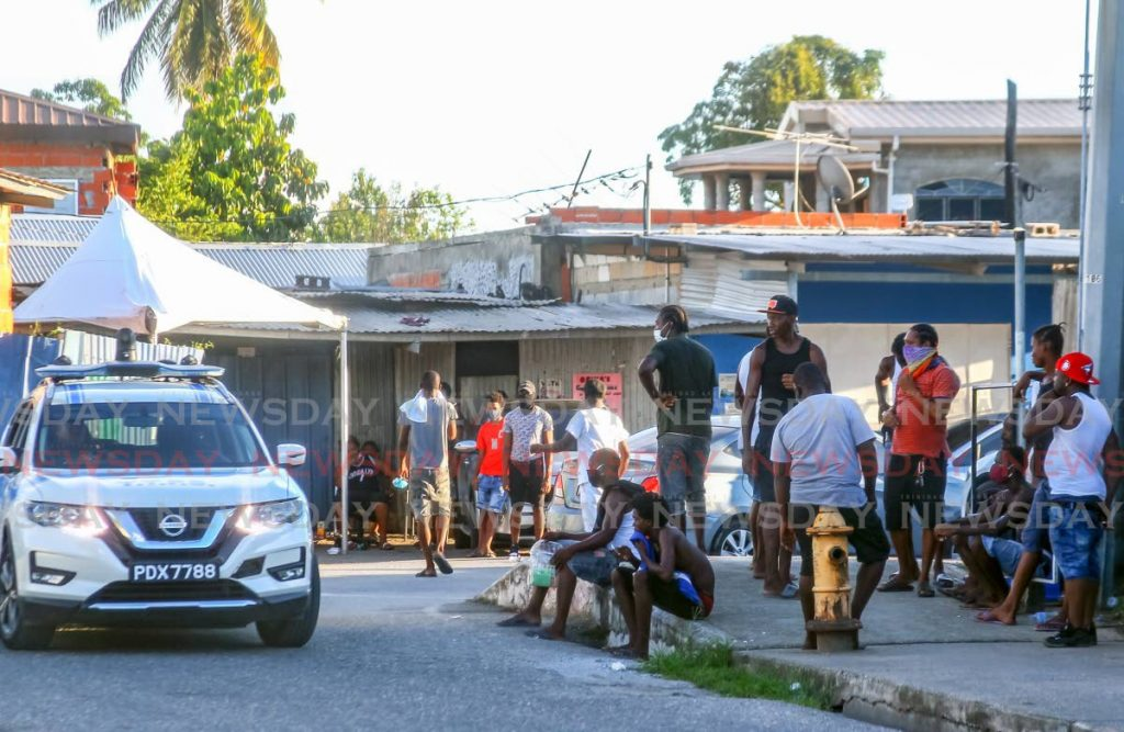 A Police patrol passes near the home of Cedric 'Burkie' Burke (inset), where neighbours gathered in the street on hearing the new of his death, believed to be at the hands of covid19, on Production Drive, Sea Lots, on Friday. - ROGER JACOB