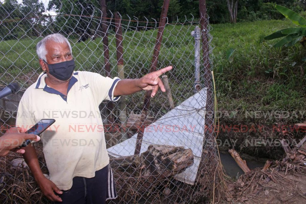 Sheriff Mohammed, a resident of Ragoobar Trace, Gasparillo, points to bad drainage next to his home which caused major flooding after recent heavy rainfall. - CHEQUANA WHEELER