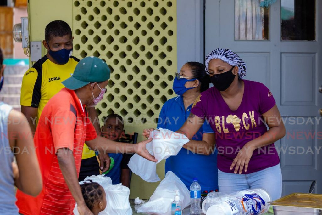 Mason Hall Government Primary School teacher Melissa Dwarika, right, serves customers while assisted by some of her colleagues, relatives and friends at her home in Collier Trace, Glen Road on Saturday.  - DAVID REID