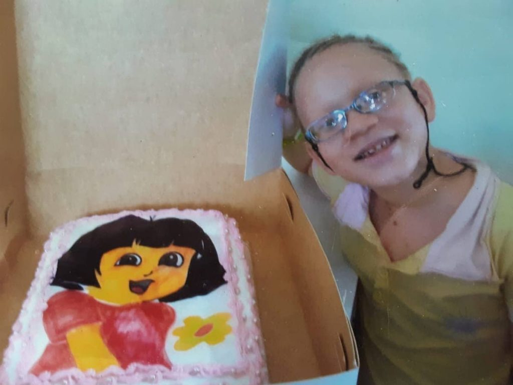 Shindlar Cuffy smiles while standing by the cake which was bought to celebrate her eighth birthday. -