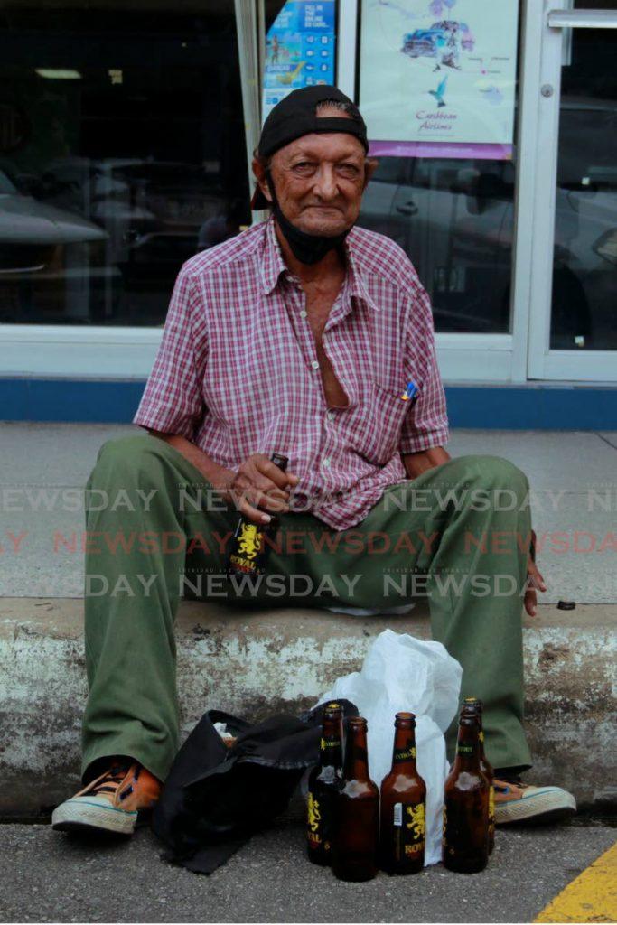 No bar, no problem: Amzail Rosan pulls down his mask to have a few drinks at Carlton Center, carpark San Fernando. - Marvin Hamilton