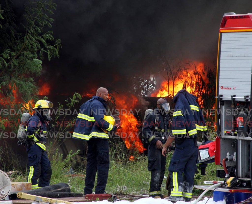 Members of the Trinidad & Tobago Fire Service, prepare to extinguish a fire in Pioneer Drive, Sealots on Thursday afternoon. - Angelo Marcelle
