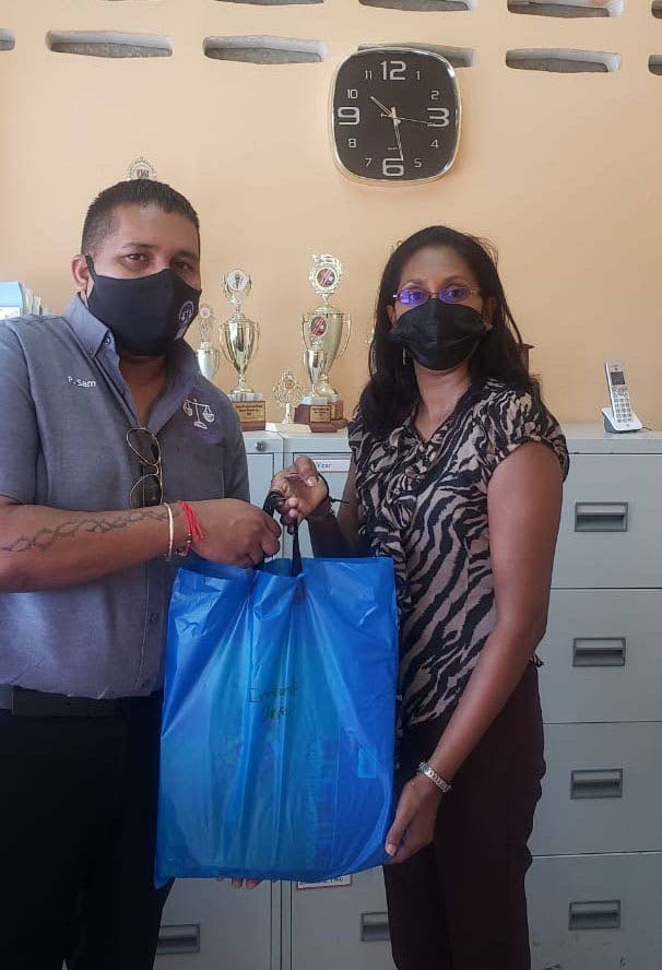 HELPING HAND: Preston Sam, managing director of Advanced Taxation and Business Services Ltd, makes a donation of stationary hampers to Theresa Motilal, Principal of the Jubilee Presbyterian School in Guaico, Tamana. PHOTO COURTESY ADVANCED TAXATION AND BUSINESS SERVICES LTD -