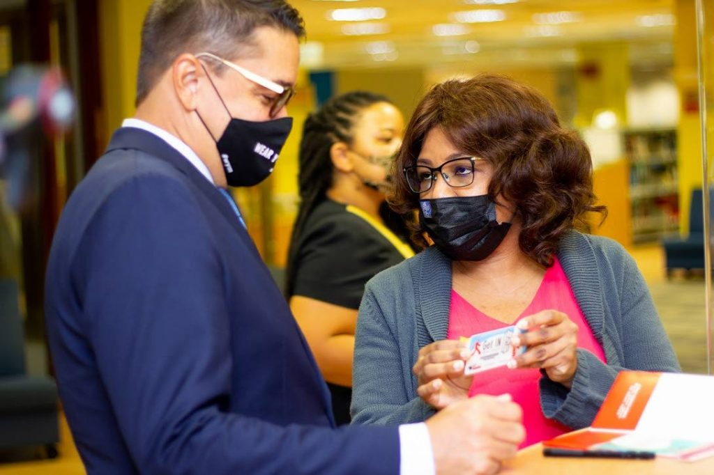 Librarian Brigid Winters, right,  of the Port of Spain Adult Library  explains the benefits of using the Nalis library card to Minister Symon de Nobriga.  The Minister received his very own card. -