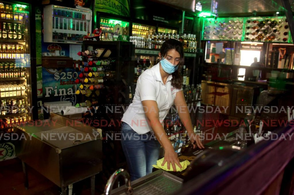 Bartender Marcy Ledel at Hutt Shutts in Tacarigua does some cleaning even though the bar was closed due to covid19 restrictions on gatherings. - SUREASH CHOLAI