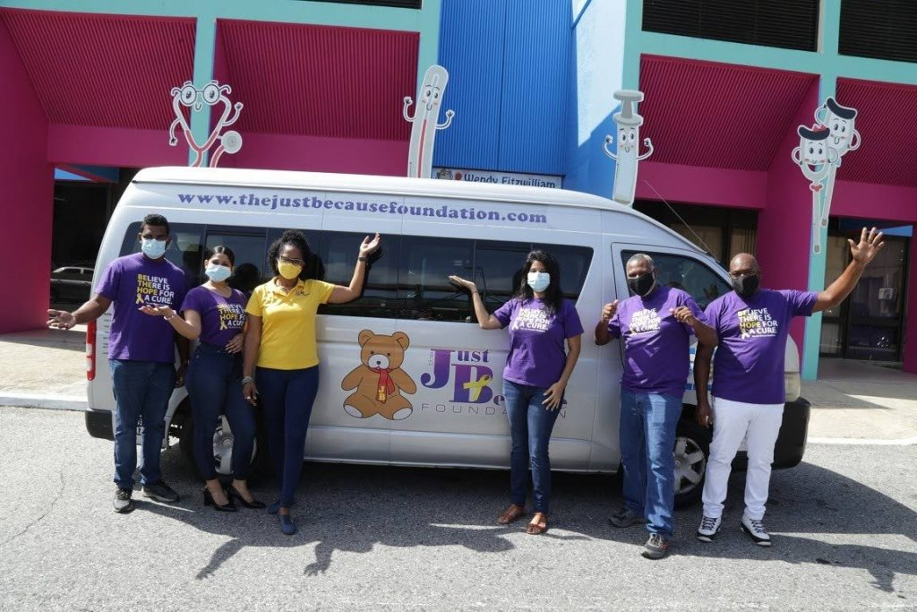 The Just Because Team stand in front of one of its vehicles used to transport cancer  patients and their families to and from the hospital. -