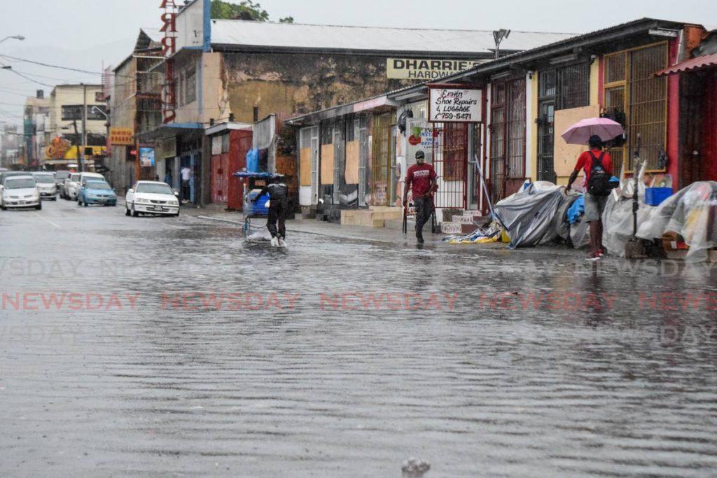Pedestrians walk through floodwater on Henry Street, Port of Spain on Saturday morning. Torrential showers triggered flash flooding across Trinidad. - Vidya Thurab