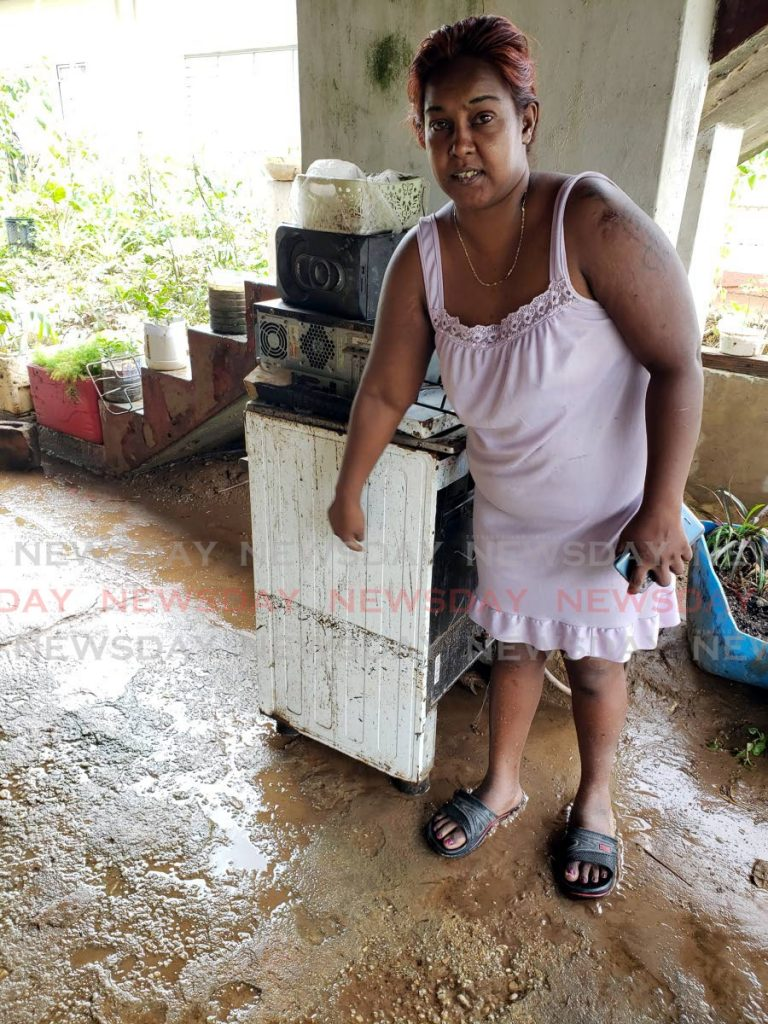 Claudette Bissoon shows the height of where floodwaters rose before abating in the yard of her home on the Eastern Main Road, Arouca on Saturday. -