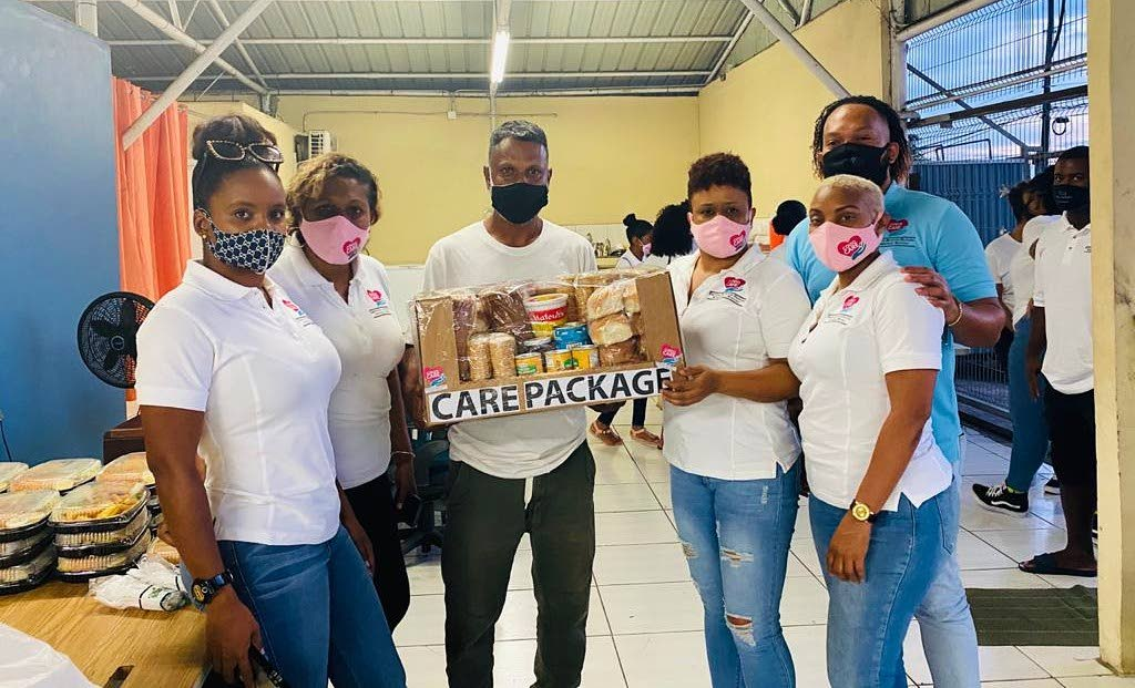 A representative of the San Fernando Centre for Displaced Persons, receives a care package from Covid Care founder Natasha Noreiga, third from right, with other members Roxanne Sealey, left, Cheryl Noreiga, Jaylon Lynch and Summer Boyce.    -