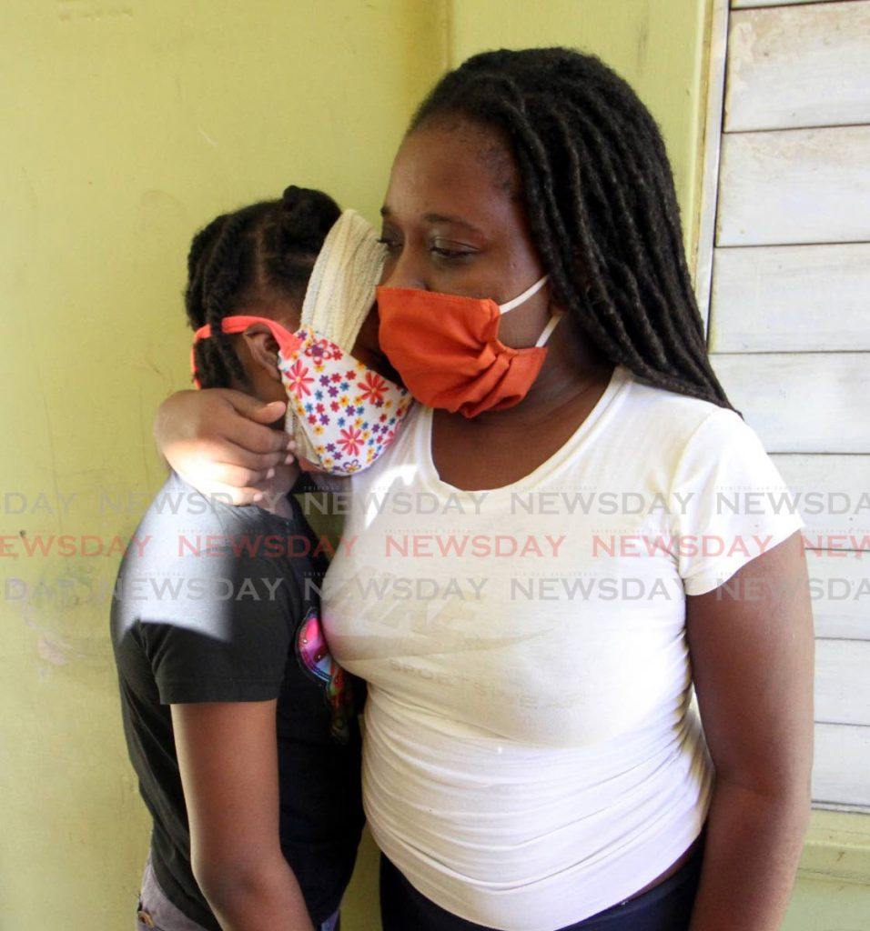 SUPPORT: HDC Maloney Gardens resident Amanda Baptiste consoles her daughter Tashanna at their home on Monday, five days after the child was injured by a piece of ceiling which fell on her head. Photo by Angelo Marcelle -