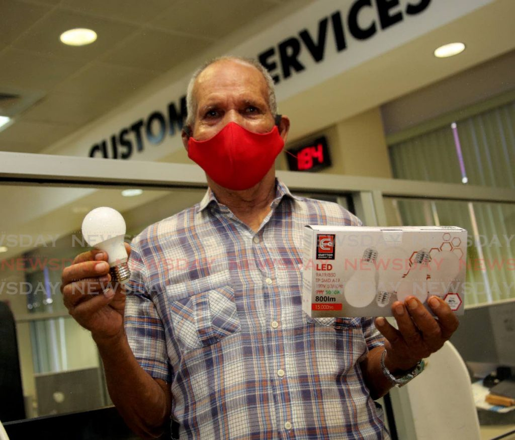 TTEC customer Hugh Ramsey shows the free LED bulbs he collected at TTEC's Park St, Port of Spain payment centre on September 22.  - SUREASH CHOLAI