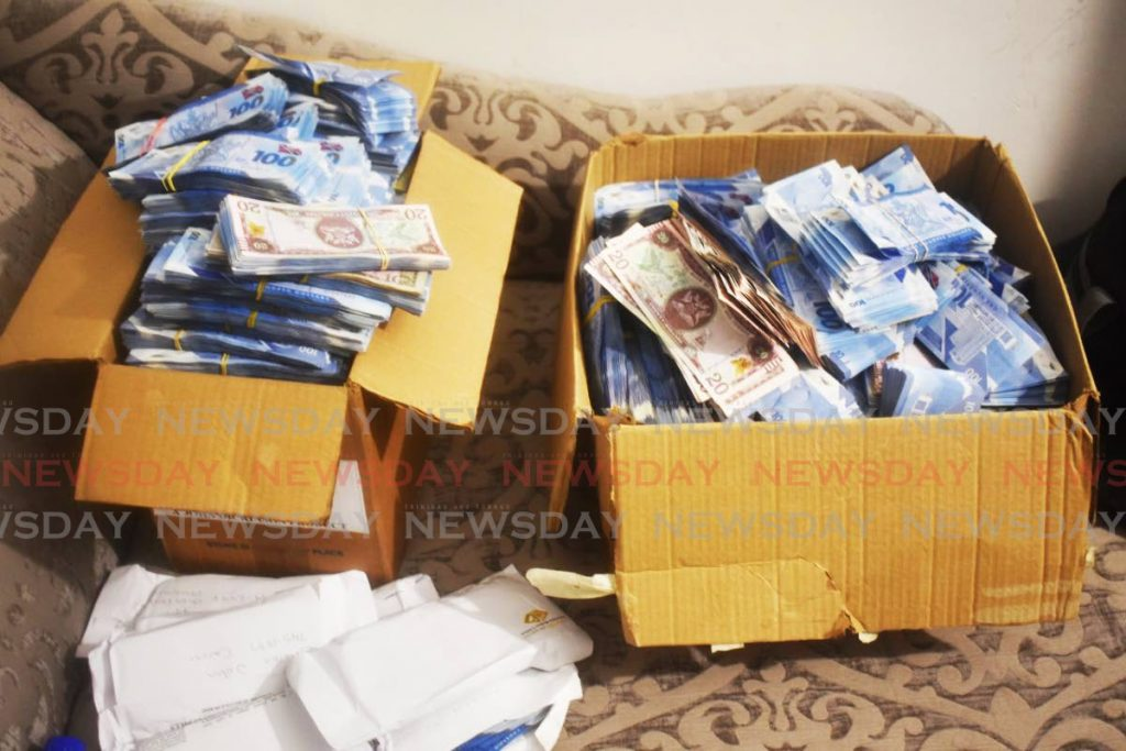 Two cardboard boxes filled with cash seized by police at a building in La Horquetta on Tuesday. Other containers filled with cash were found hidden at the building. PHOTO COURTESY TTPS -