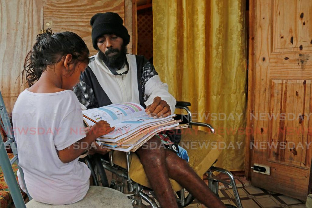 In his wheelchair at his Tableland home on Wednesday, Ryan Abdool helps his 6-year-old daughter Isabella with her schoolwork. - Marvin Hamilton