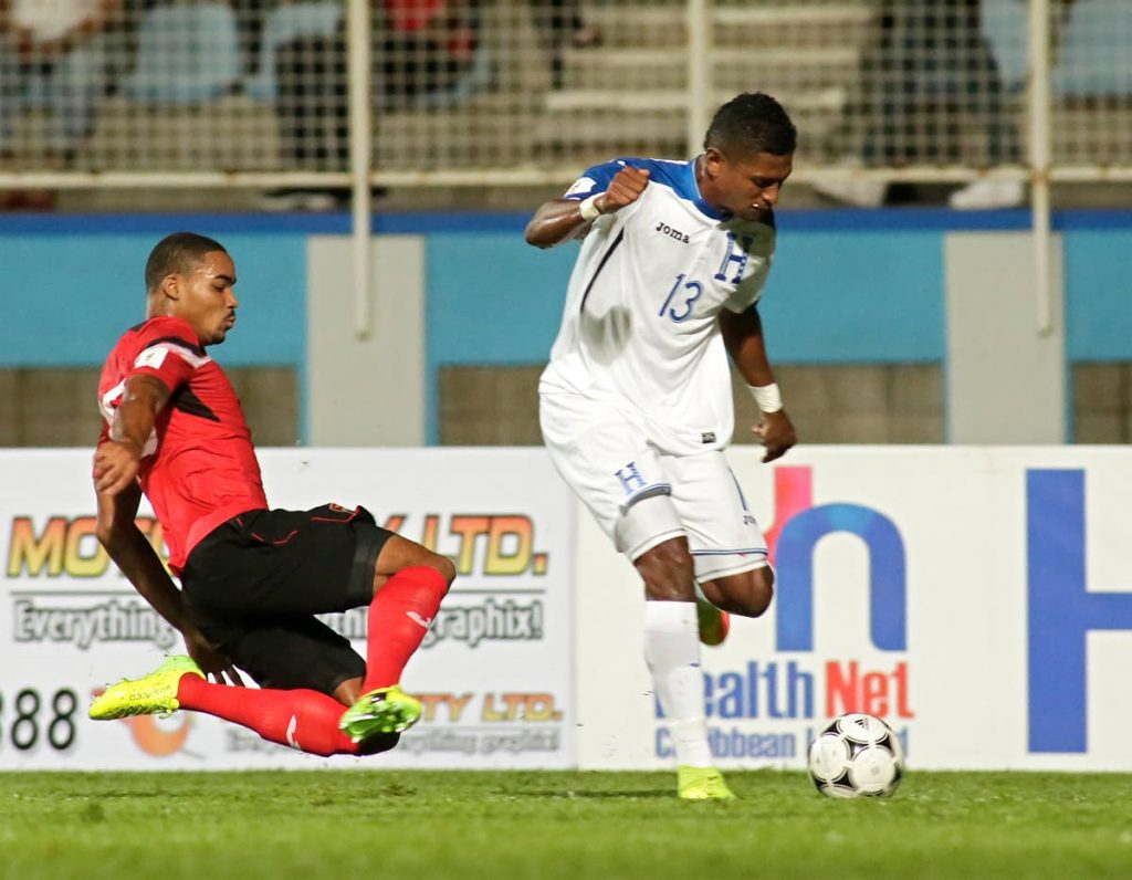 In this September 1, 2017 file photo, Honduras' forward Carlo Costly (right) runs with the ball past TT defender Alvin Jones during the teams' FIFA World Cup 2018 CONCACAF qualifiers match at the Ato Boldon Stadium, Couva. (AFP PHOTO) -