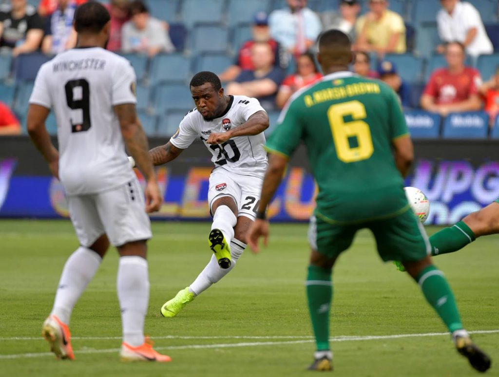 In this June 26, 2019 file photo, Jomal Williams (C) of TT shoots on goal as teammate Shahdon Winchester (L)  and Ronayne Marsh-Brown of Guyana look on during the Concacaf Gold Cup Group D match, at Children's Mercy Park in Kansas City, Kansas. - AFP PHOTO