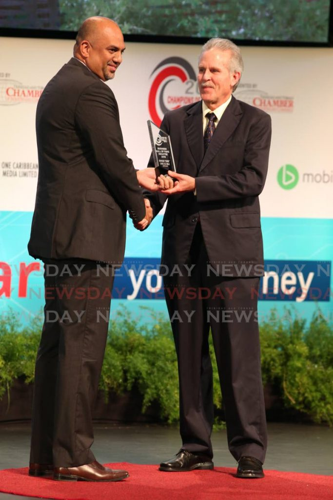 In this 2019 file photo, Guardian Life of the Caribbean president Anand Pascal presents John Hale with an award for his father, former president/CEO of Hand Arnold, Osmond 'Ossie' Hale, after he was posthumously inducted into the TT Chamber's Hall of Fame, at the Chamber's Champions of Business Awards ceremony. -