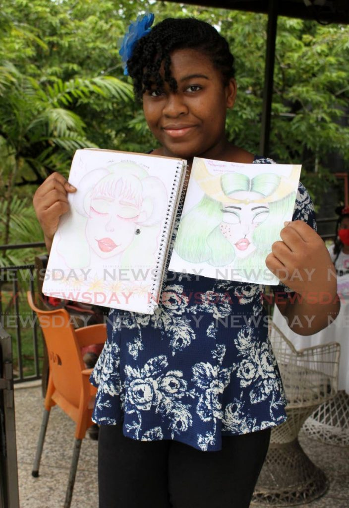 Symmya Hyde holds two of her anime drawings at her home in Brazil. She learned the Japanese art on YouTube.  PHOTOS BY ANGELO MARCELLE  -