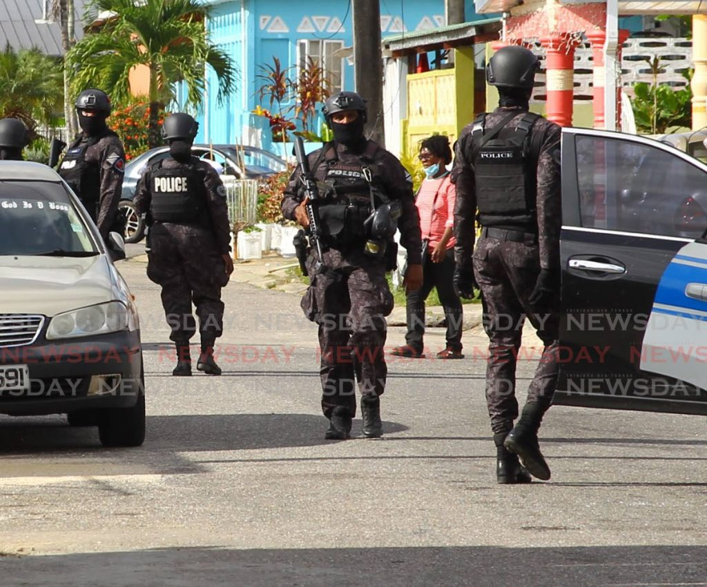 In this September 23, 2020 file photo, members of the Special Operations Response Team take part in the search of a house in La Horquetta in the $22 million sou-sou investigation. -