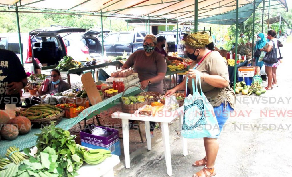 A customer makes a purchase at a vegetable stall at the Green Market. - SUREASH CHOLAI