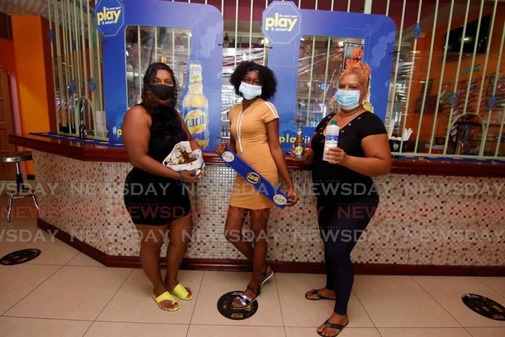 Gloria's Bar owner Gloria Boodram, right, and her workers display take-away bags and sanitisers donated by Carib Brewery. On the bar counter are screens also donated by the brewery. -