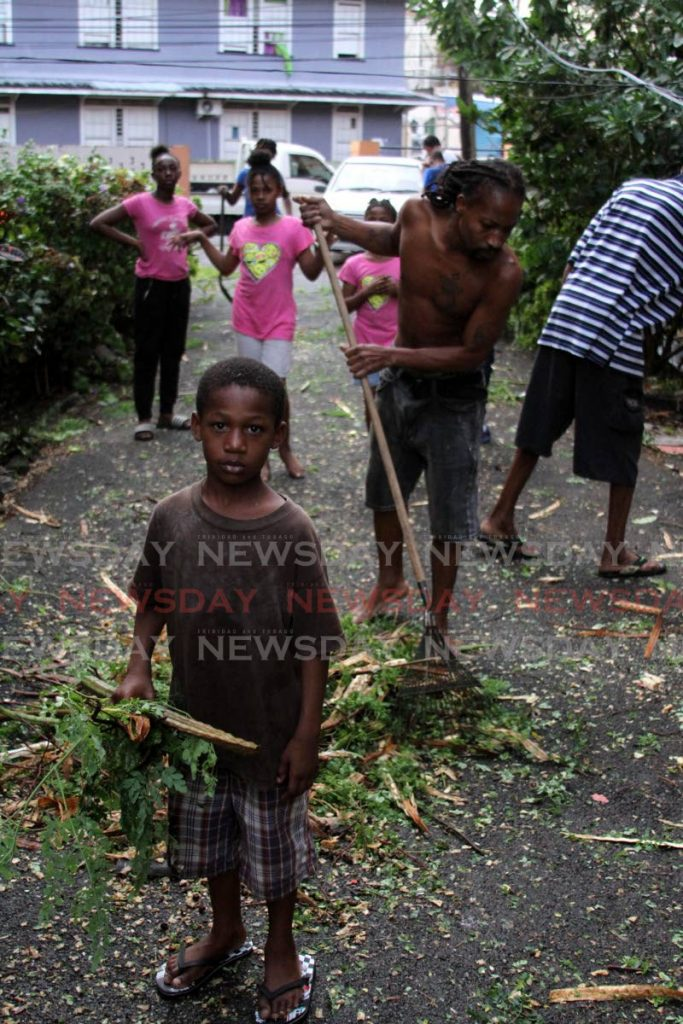 CLEAN UP: A boy holds a branch while others clean up Nelson Street after the freak storm on Wednesday brought down trees and tore the roofs off several houses. PHOTO BY ANGELO MARCELLE - Angelo Marcelle