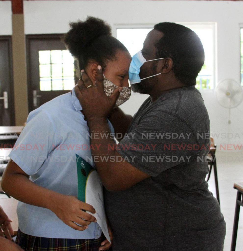 PROUD FATHER: SEA student Mpule Edwards is kissed by her father Daryl after the SEA results on Thursday. Mpule passed for St Joseph Convent, St Joseph. PHOTO BY ANGELO MARCELLE - Angelo Marcelle