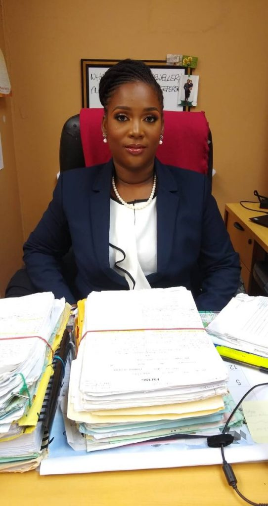 Danielle Thompson behind a case files at work in the Office of the Director of Public Prosecution. -