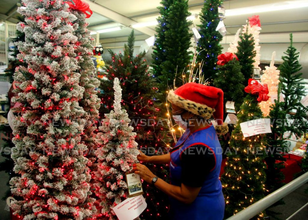 With the yuletide season fast approaching, Sharon Clement is making sure the Christmas trees on display for sale looks the best at her workplace at Excellent Stores in  Excellent City Centre, Frederick Street, Port of Spain. - SUREASH CHOLAI