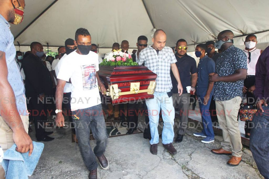 Mourners carry the casket of prisons officer Joel Ramsoondar at his funeral on Friday held at his mother's Chaguanas home. - Lincoln Holder