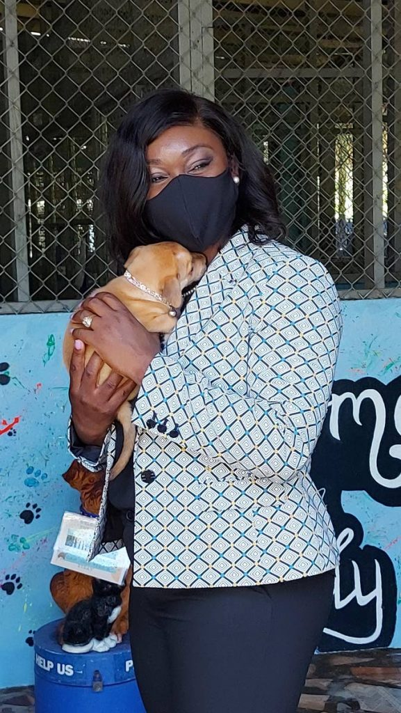 Health Secretary Tracy Davidson-Celestine hugs a puppy at the Tobago Society for the Prevention of Cruelty to Animals in Scarborough on Friday. -